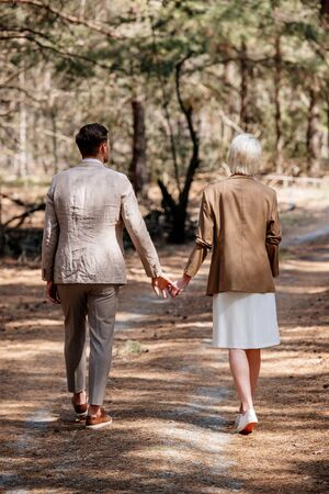back view of stylish couple holding hands and walking in forest 版權商用圖片