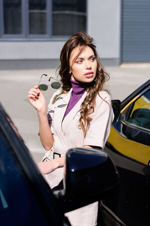 selective focus of serious young woman holding sunglasses near cars Stock Photo