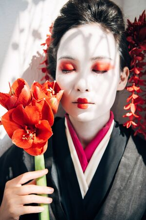 portrait of beautiful geisha holding red flowers in sunlight