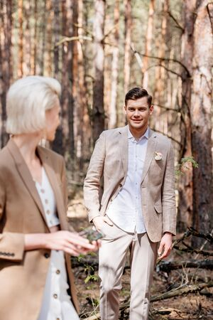 smiling bridegroom standing with hand in pocket and looking at bride in forest