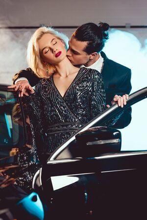 stylish man kissing beautiful sensual woman near car Stock Photo