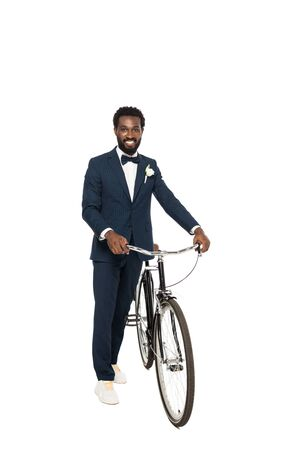 cheerful african american man in suit standing with bicycle isolated on white 写真素材
