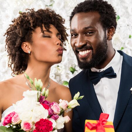african american bride with duck face holding bouquet with flowers near happy bridegroom