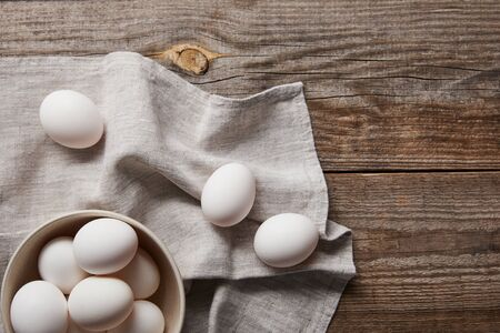 top view of chicken eggs in bowl on wooden table with cloth