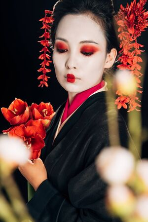 selective focus of beautiful geisha in black kimono with red flowers and sakura branches isolated on black