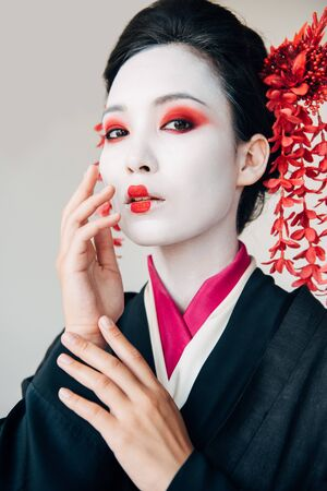 beautiful geisha in black kimono with red flowers in hair touching face isolated on white 版權商用圖片