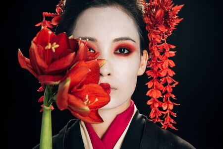portrait of beautiful geisha in black kimono with red flowers isolated on black
