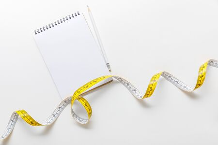 top view of measuring tape, blank notebook with pencil on white background