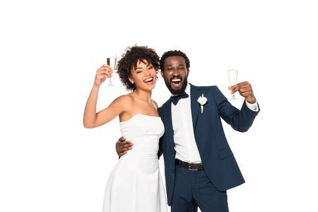 happy african american bride and bridegroom holding champagne glasses isolated on white