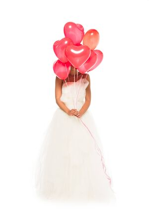 african american bride covering face with heart-shaped balloons while standing in wedding dress isolated on white Stockfoto