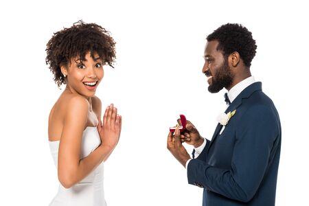 Alegre hombre afroamericano sosteniendo una caja con anillo mientras hace una propuesta a una mujer sorprendida aislada en blanco Foto de archivo
