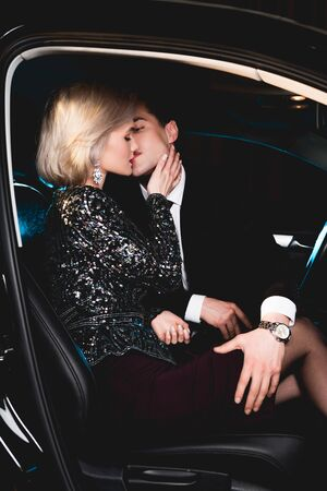 stylish man kissing beautiful sensual young woman in car