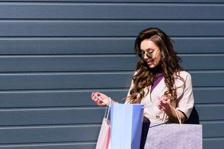 cheerful curly young woman looking at blue shopping bag Banco de Imagens