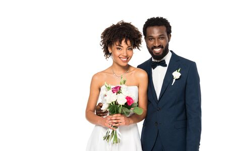 happy curly african american bride smiling while holding bouquet near bridegroom isolated on white