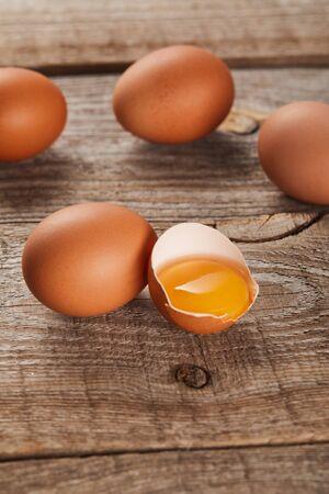 broken eggshell with yellow yolk near eggs on wooden table