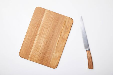 top view of empty wooden chopping board and knife on white background