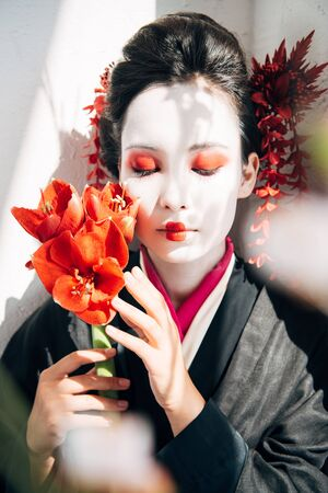 selective focus of sakura branches and beautiful geisha holding red flowers with closed eyes in sunlight
