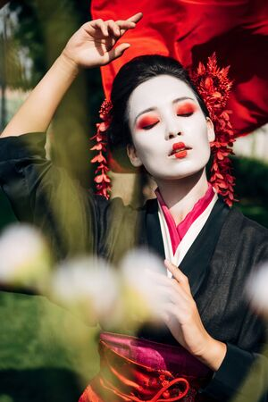selective focus of tree branches and beautiful gesturing geisha with red cloth on background in sunlight