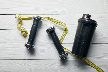 top view of black shaker cup, yellow measuring tape and dumbbells on wooden white background Standard-Bild - 128144278