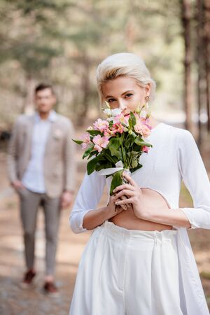 pretty bride with bouquet of flowers and bridegroom in forest