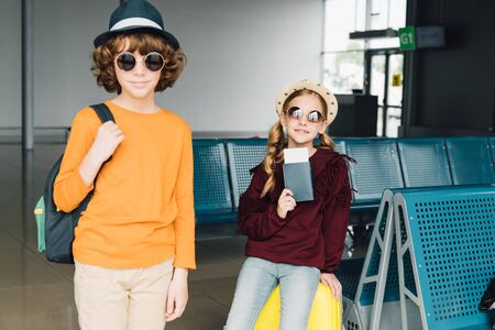 cute preteen kids in sunglasses in waiting hall with backpack, air ticket and passport