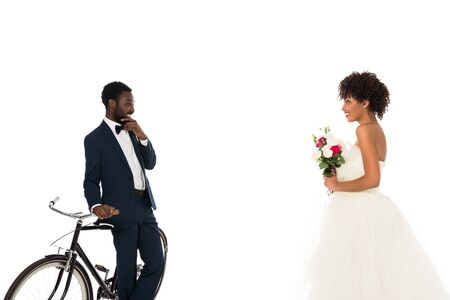 african american bridegroom standing near bicycle and looking at beautiful bride with flowers isolated on white
