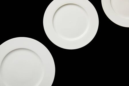 top view of white empty round plates isolated on black