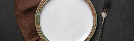 top view of vintage white empty round plate on black wooden table near brown napkin and silver fork, panoramic shot