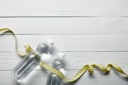 top view of bottles with water and yellow measuring tape on wooden white background with copy space