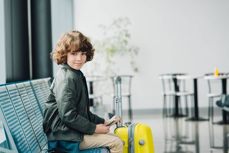 boy sitting on blue seat, holding passport and yellow suitcase and looking at camera in waiting hall in airport
