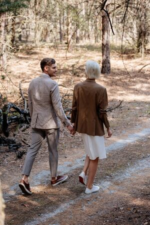 full length view of stylish couple holding hands and walking in forest