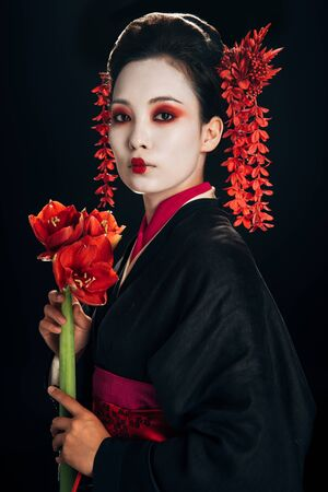 beautiful geisha in black kimono with red flowers isolated on black