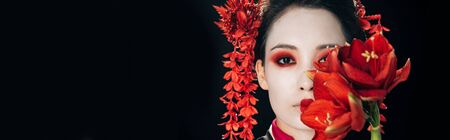 portrait of beautiful geisha in black kimono with red flowers isolated on black, panoramic shot Stock Photo