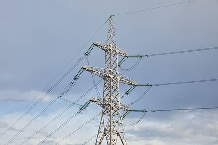 view of electric pole with long wires on grey sky background
