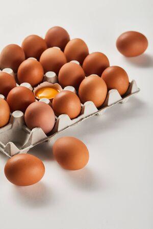 broken eggshell with yellow yolk near eggs in carton box