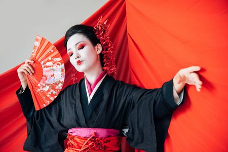 beautiful geisha in black kimono with hand fan and red cloth on background dancing isolated on white 写真素材