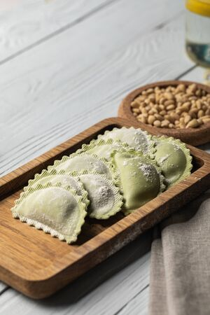 close up view of raw green ravioli with flour on wooden board near pine nuts