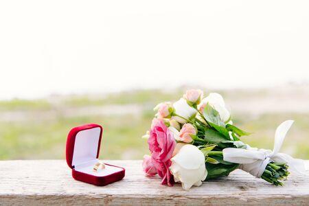 Ehering in roter Box und Blumenstrauß auf Holzoberfläche