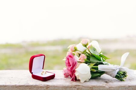 wedding ring in red box and bouquet on wooden surface