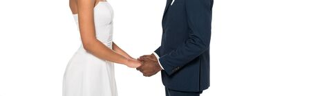panoramic shot of african american bridegroom and bride holding hands while standing isolated on white