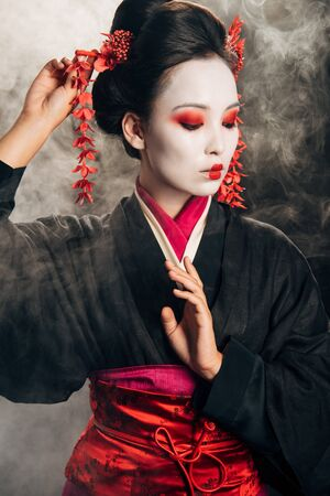 geisha in black kimono with red flowers in hair gesturing on black background with smoke