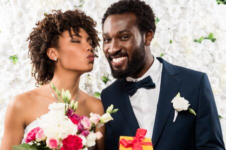 Afro-Amerikaanse bruid met eendengezicht met boeket met bloemen in de buurt van vrolijke bruidegom Stockfoto