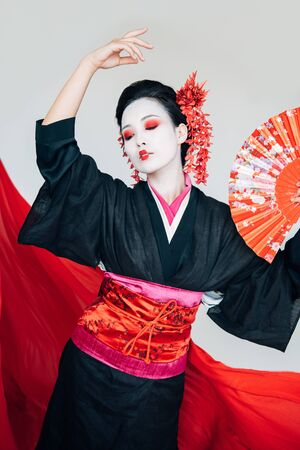 beautiful geisha in black kimono with hand fan dancing near red cloth on background isolated on white Stock Photo