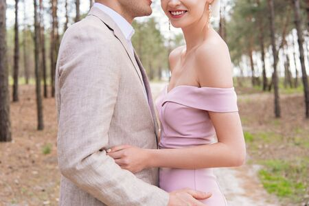 cropped view of happy just married couple embracing in forest with smile Banco de Imagens