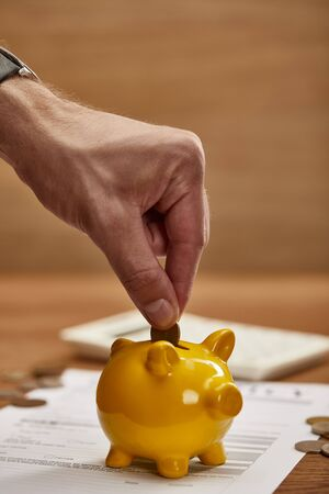 partial view of man putting coin in yellow piggy bank