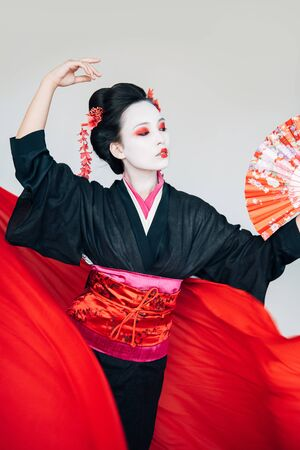 geisha in black kimono with hand fan and red cloth on background dancing isolated on white