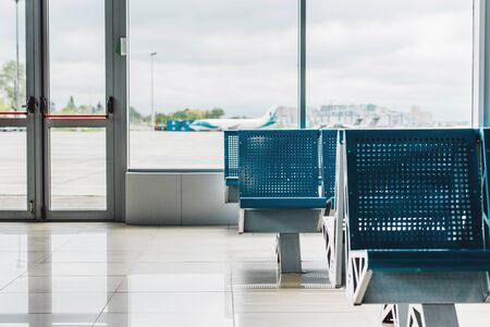 waiting hall in airport with blue seats and window