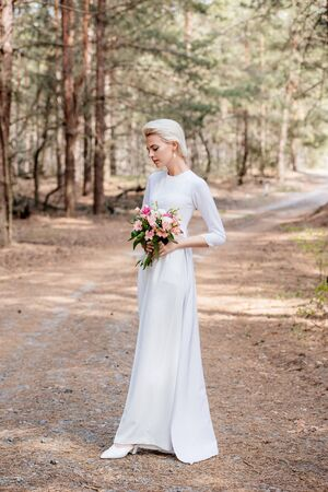 full length view of beautiful bride holding wedding bouquet in forest Stok Fotoğraf
