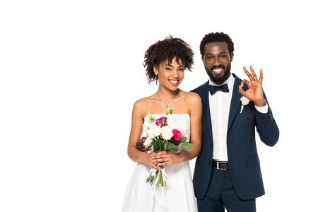happy african american bride holding bouquet near bridegroom showing ok sign isolated on white 免版税图像