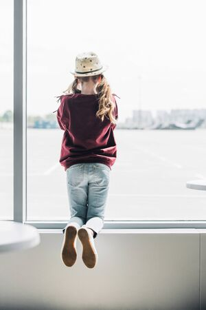 Back view of preteen kid in hat on window during daytime Stock Photo